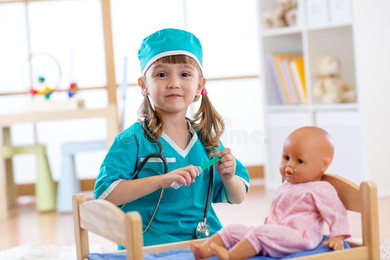 En aktiv förskole- barnliten flicka som kläs som doktorslekar med hennes docka royaltyfria foton