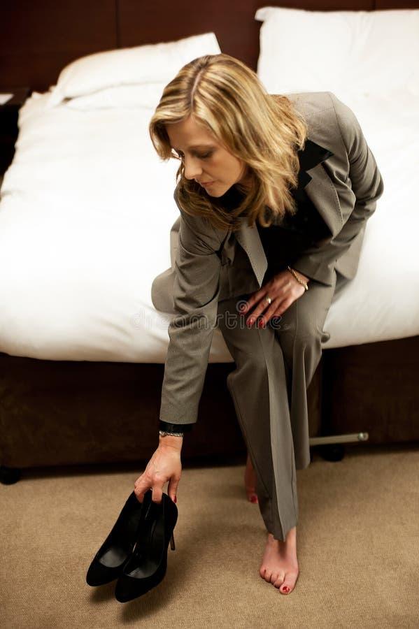 En aktiv kvinna som håller henne foten, slitage åt sidan royaltyfria bilder