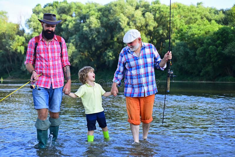 En aktiv livsstil utomhus Farfar med son och sonson som har kul i floden Grattis pappers dag Fiske Sommardag royaltyfria foton