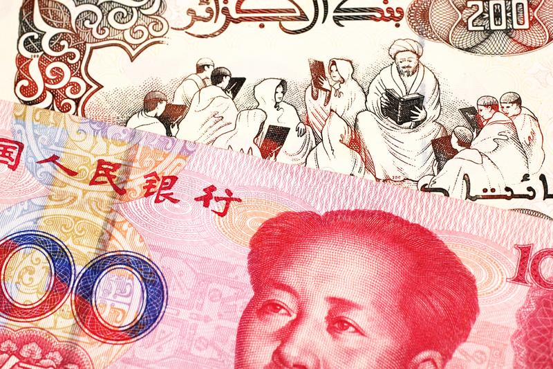 En algerisk dinar med en kinesisk yuananmärkning royaltyfria bilder