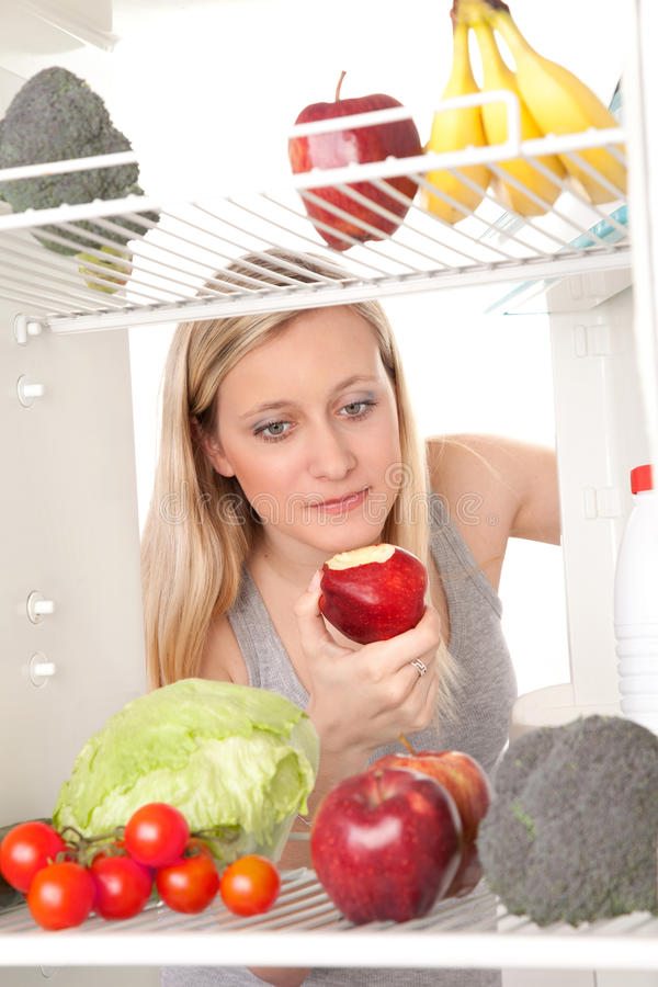 En alimento de mirada adolescente en refrigerador fotos de archivo libres de regalías