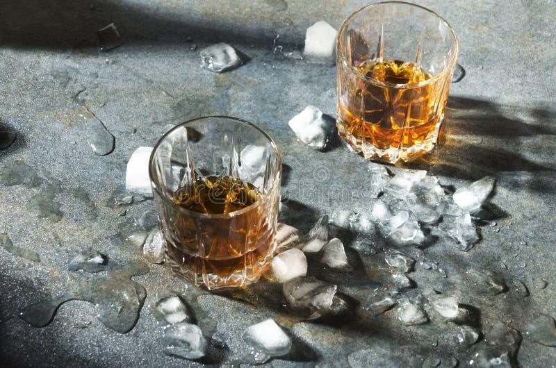 En alkoholdrink och is Whisky med stycken av is Exponeringsglas med en stark dryck fotografering för bildbyråer