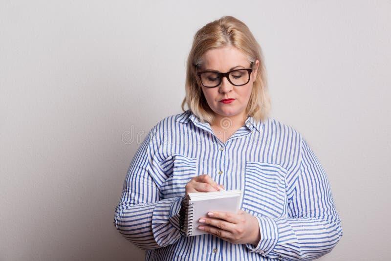 En allvarlig blond överviktig kvinna med exponeringsglas och en notepad som gör anmärkningar fotografering för bildbyråer