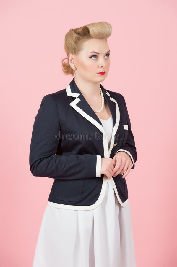 En allvarlig blond flicka i omslag ser upp Kvinna i utvikningsbildstil som drömmer att stå i studio med stängda händer royaltyfri foto
