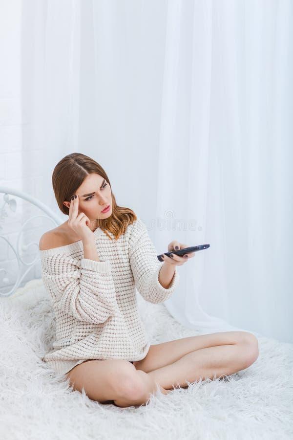 En allvarlig flicka, sitter på en säng med en ledsen och längtande blick och kopplar TVfjärrkontrollen arkivfoton