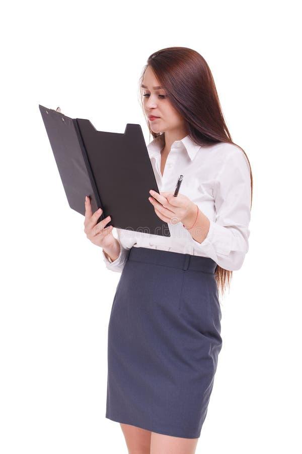 En allvarlig flicka som ser i en mapp med legitimationshandlingar bakgrund isolerad white royaltyfri foto