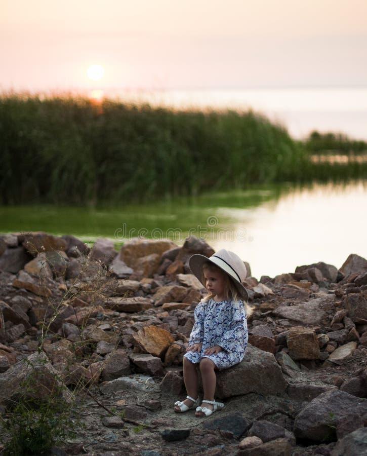 En allvarlig liten flicka i en hatt sitter på en stenig bank nära en flod arkivfoton