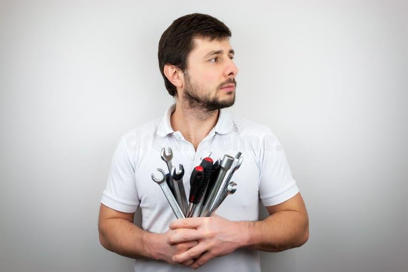 En allvarlig skäggig man i en vit t-skjorta med en bukett av skiftnycklar och skruvmejslar som ser till sidan royaltyfri fotografi