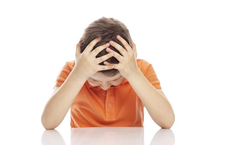 En allvarlig skola-ålder pojke i en ljus orange polot-skjorta sitter på en tabell som knäpper fast hans huvud i hans händer Förtv royaltyfria foton