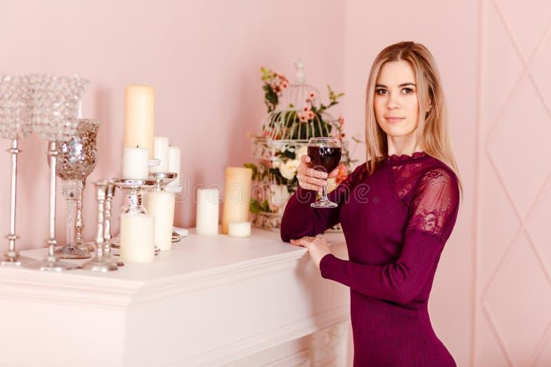 En allvarlig spenslig tjugo-år-gammal kvinna står vid spisen och rymmer ett exponeringsglas av rött vin i hennes hand royaltyfri foto