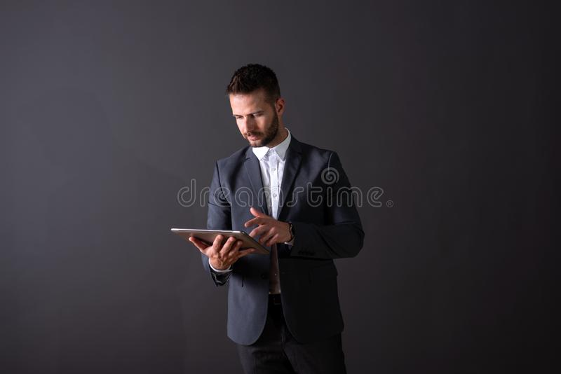 En allvarlig stilig affärsman som använder en minnestavla royaltyfria bilder