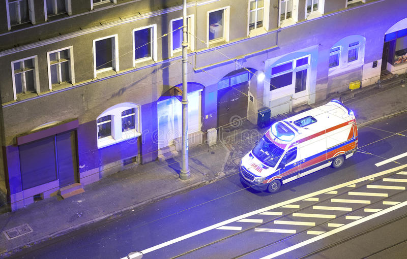 En ambulans med blinkande ljus som framme står av en buildin royaltyfria bilder