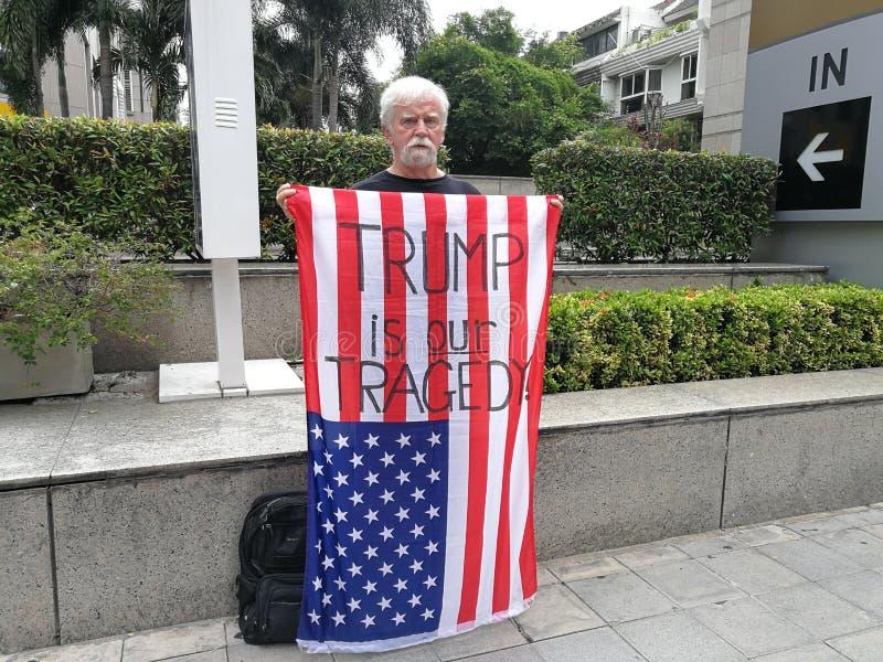 En amerikansk manshow amerikanska flaggan med ord`-TRUMFEN ÄR VÅR TRAGEDI ` På den trådlösa vägen nära USA-ambassaden i Thailand arkivfoto