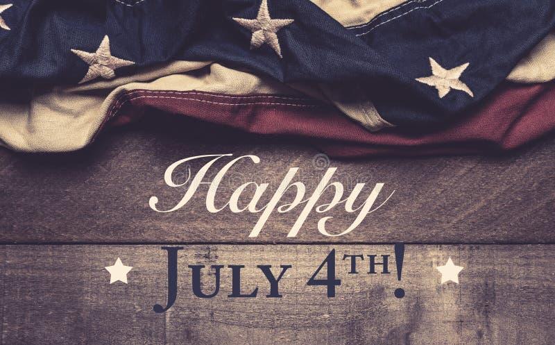En amerikanska flaggan eller en bunting på en träbakgrund med den Juli 4th hälsningen arkivfoton