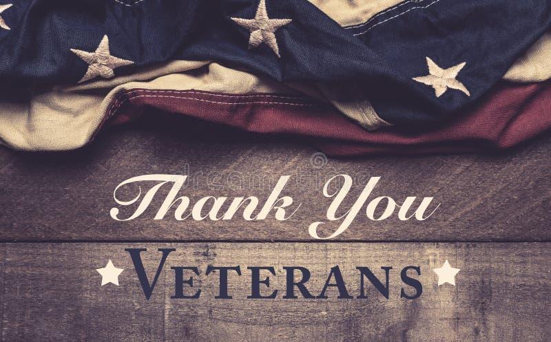 En amerikanska flaggan eller en bunting på en träbakgrund med hälsning för dag för veteran` s arkivfoton