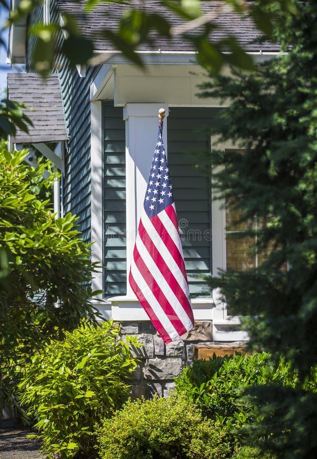 En amerikanska flaggan som framtill hänger av ett hem i en grannskap royaltyfri fotografi