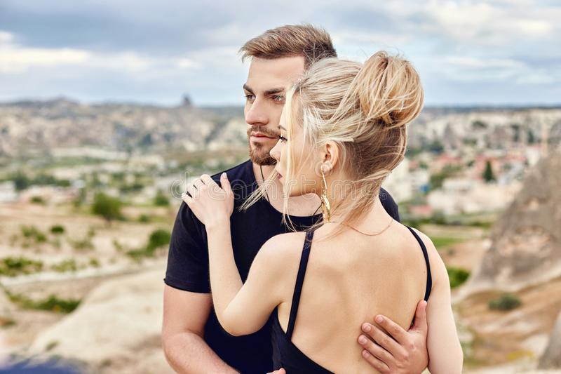 En amor el par del este en montañas de Cappadocia abraza y los besos Amor y emociones que aman los pares vacationing en Turquía p foto de archivo