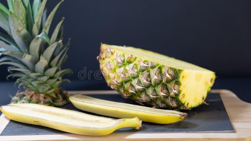 En ananashalva på ettinramat stenbräde klipps i halvan, omkring två halvor av en banan royaltyfri fotografi