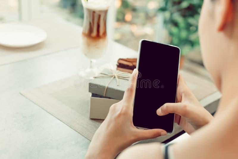 En anmärkning för kvinnabruksmobiltelefon för kort och arbeta i coffee shop royaltyfri foto