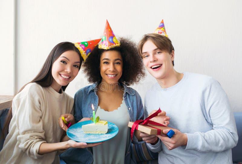 En annan bild av en födelsedagflicka och hennes vänner Den asiatiska flickan har ett stycke av kakan Grabben rymmer en gåva i han royaltyfria foton