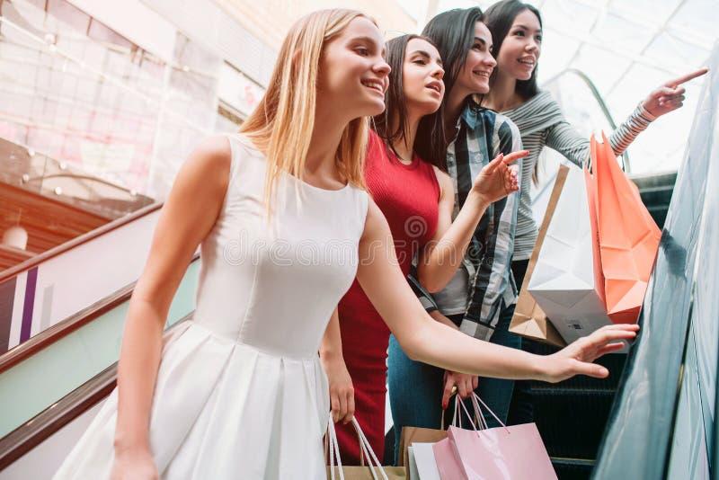 En annan bild av flickor som står på trappa De ser högra och att le Några av dem har shoppingpåsar i deras arkivfoton