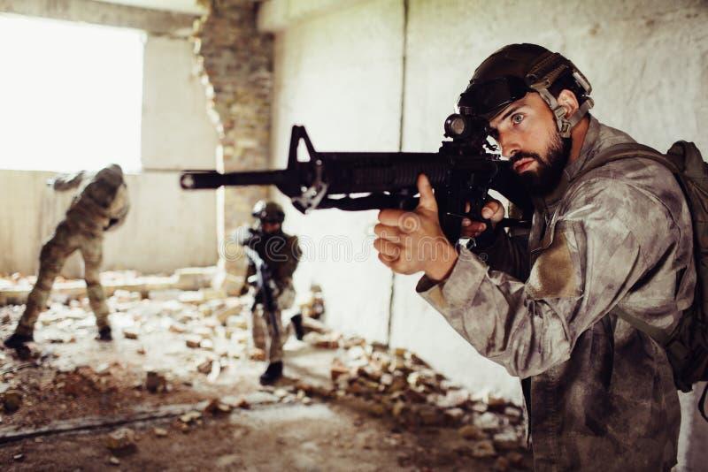 En annan bild av modiga soldater Den skäggiga mannen står framme med geväret Den andra grabben står i mitt av royaltyfria bilder