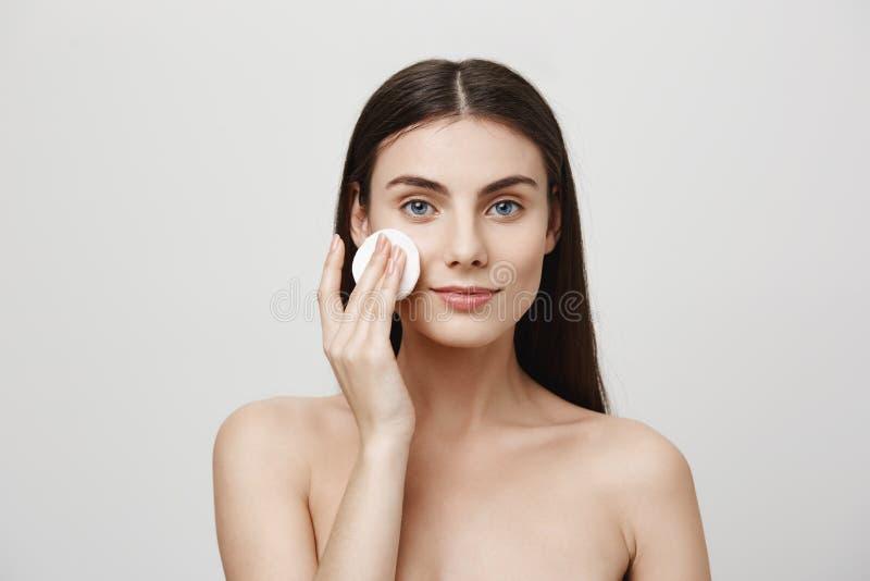 En annan dag av stridighet för skönhet Inomhus skott av den härliga unga europeiska kvinnan som av tar makeup med bomullsblocket royaltyfri bild