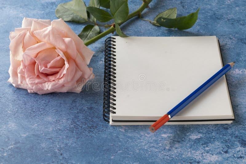 En anteckningsbokåtlöje upp med en ros arkivfoton