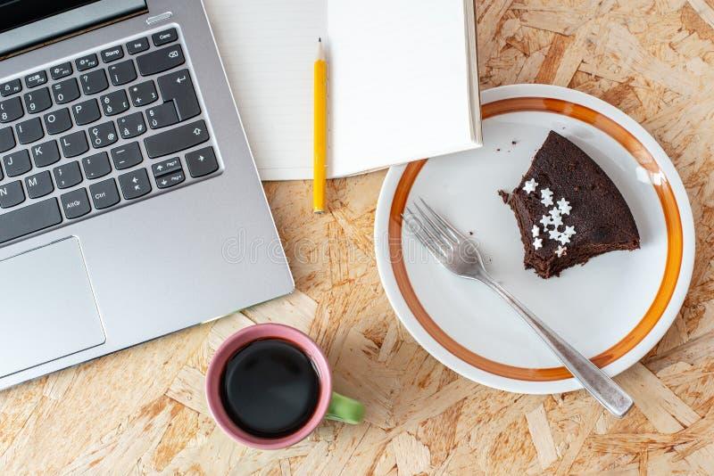 En anteckningsbok, en kopp kaffe, en platta med en chokladkaka, en anteckningsbok med en blyertspenna p? ett tr?skrivbord i busen arkivfoto