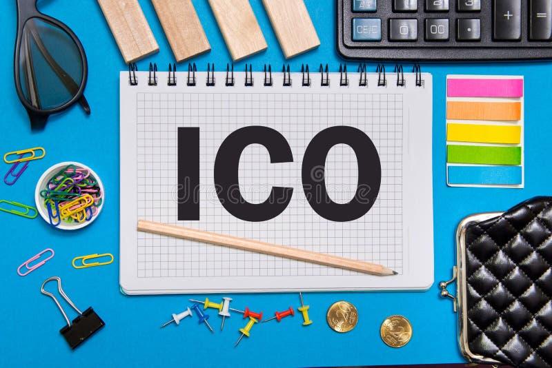 En anteckningsbok med myntet för affärsanmärkningsinitial som erbjuder ICO med kontorshjälpmedel på blå bakgrund royaltyfria foton