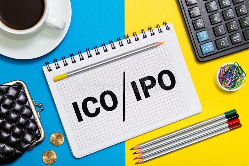 En anteckningsbok med myntet för affärsanmärkningsinitial som erbjuder ICO vs initialt offentligt erbjuda för IPO med kontorshjäl royaltyfri bild