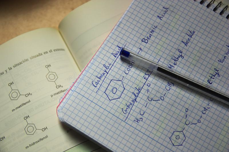En anteckningsbok och en bok med formler av organisk kemi arkivfoton