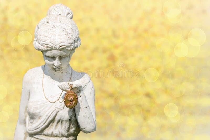 En antik guld- medaljong skallr framlagt från stenstatykvinna fotografering för bildbyråer