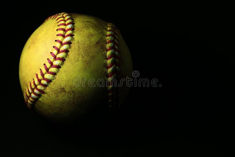 En använd gul softball som isoleras på en svart bakgrund arkivbilder