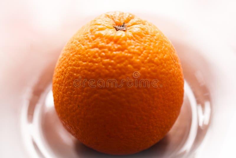 En apelsin på en platta royaltyfria foton