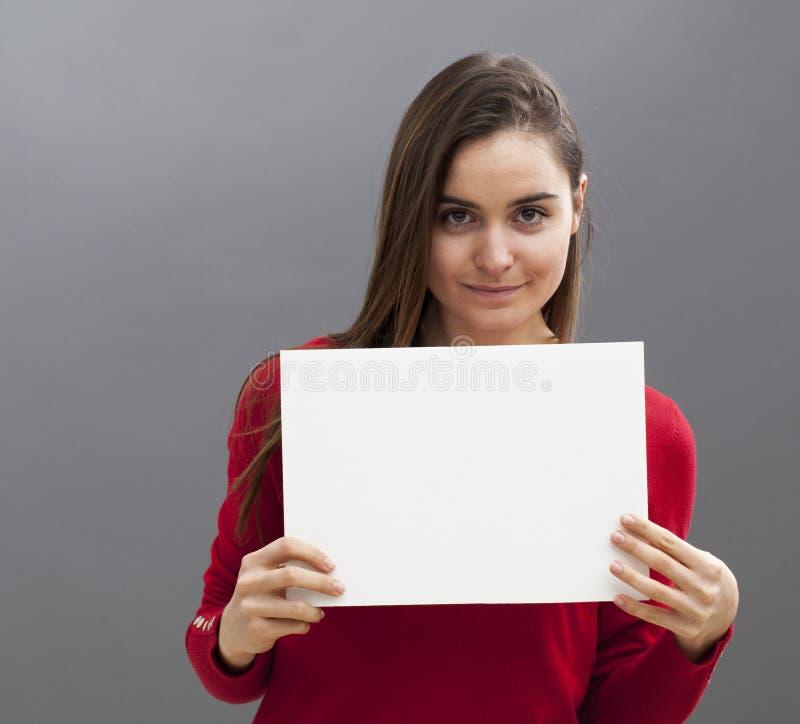 En appelant à la femme 20s de sourire faisant une publicité en montrant une insertion vide devant elle photos libres de droits