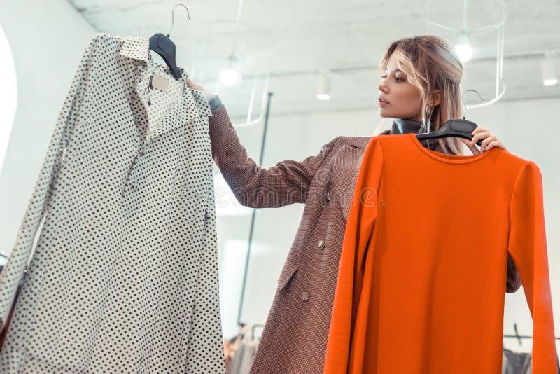 En appeler à la femme élégante utilisant la veste intéressante regardant la robe images libres de droits
