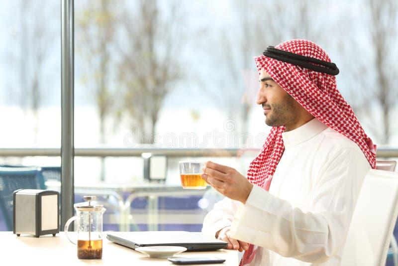 En arabisk man som njuter av en kopp te i en kaffebutik royaltyfria bilder
