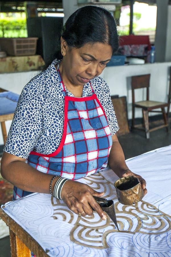 En arbetare applicerar vaxet till en batik på den Baba Batik fabriken i Matale i Sri Lanka arkivfoton