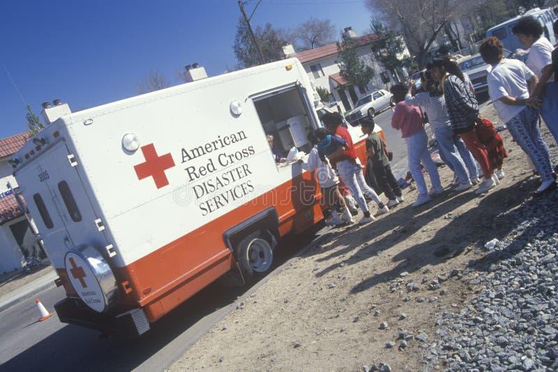 En arbetare i ett amerikanskt medel för Röda korsetkatastrofservice som ut räcker tillförsel till folk efter jordskalvet 1994 royaltyfria bilder