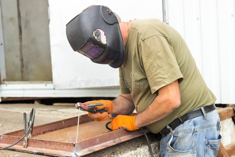 En arbetare i en svetsande maskering utför svetsande arbete på metallen Kvalitetsdelar av metall under hög temperatur royaltyfri fotografi