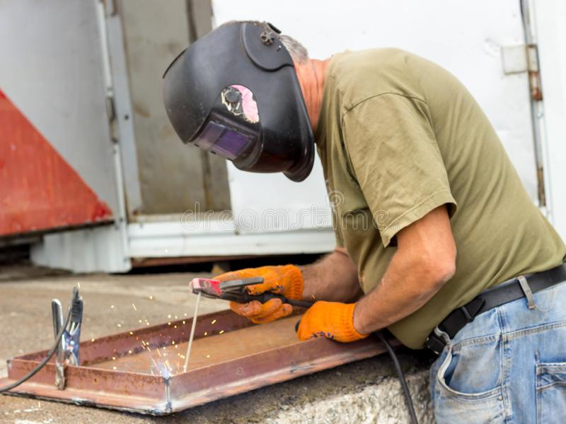 En arbetare i en svetsande maskering utför svetsande arbete på metallen Kvalitetsdelar av metall under hög temperatur arkivfoton
