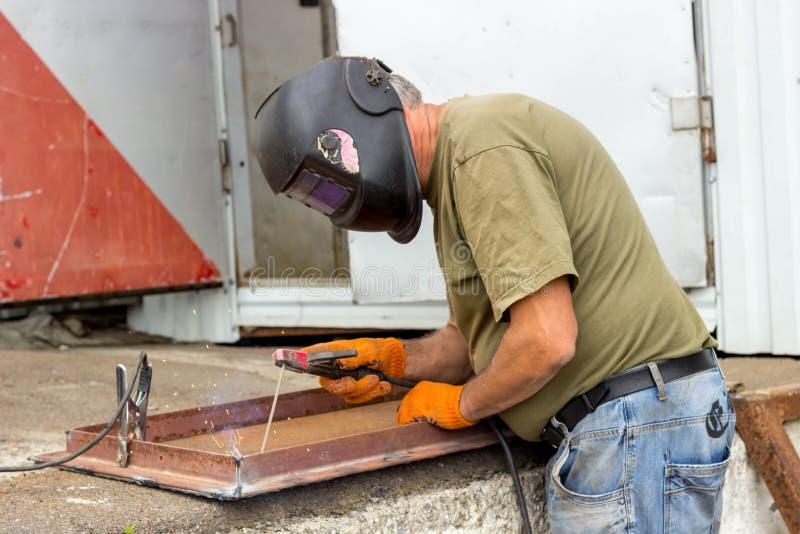 En arbetare i en svetsande maskering utför svetsande arbete på metallen Kvalitetsdelar av metall under hög temperatur arkivbilder