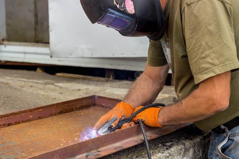 En arbetare i en svetsande maskering utför svetsande arbete på metallen Kvalitetsdelar av metall under hög temperatur royaltyfria bilder