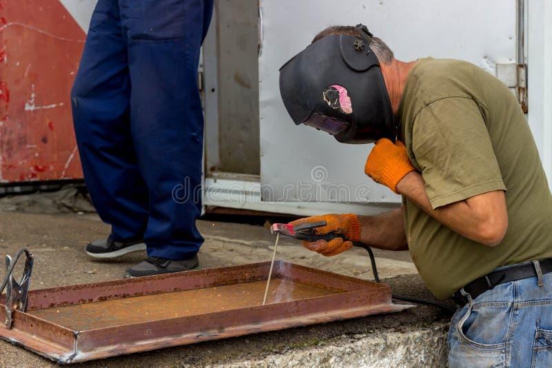 En arbetare i en svetsande maskering utför svetsande arbete på metallen Kvalitetsdelar av metall under hög temperatur arkivbild