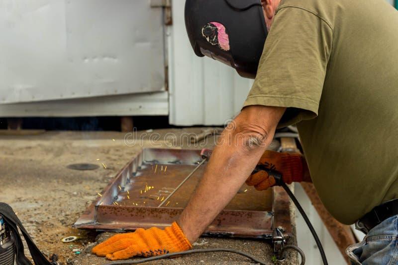 En arbetare i en svetsande maskering utför svetsande arbete på metallen Kvalitetsdelar av metall under hög temperatur fotografering för bildbyråer