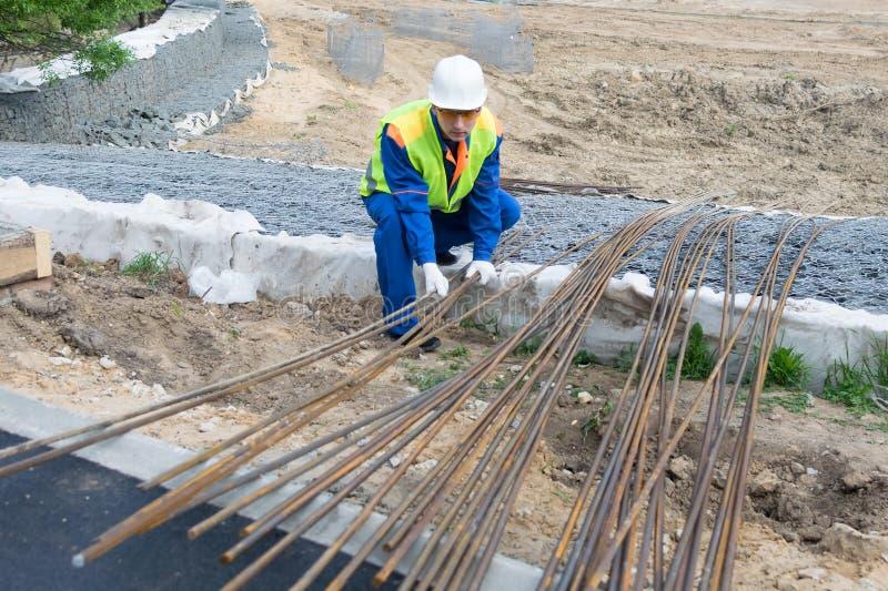 En arbetare i en vit hjälm och overaller väljer järnstänger för konstruktion arkivbild