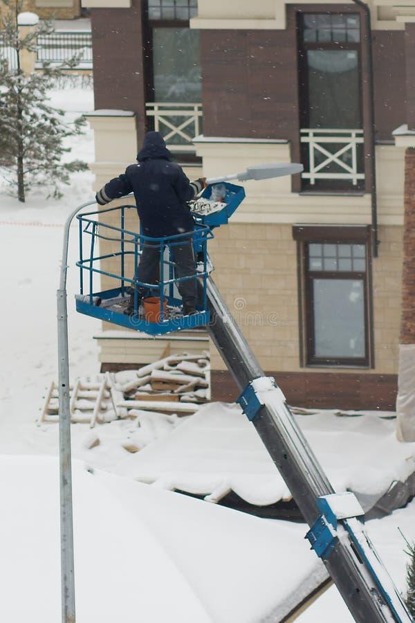 En arbetare installerar ett lyktaljus royaltyfri bild