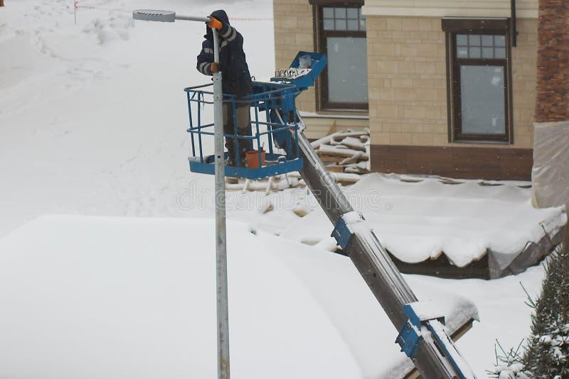 En arbetare installerar ett lyktaljus arkivbilder