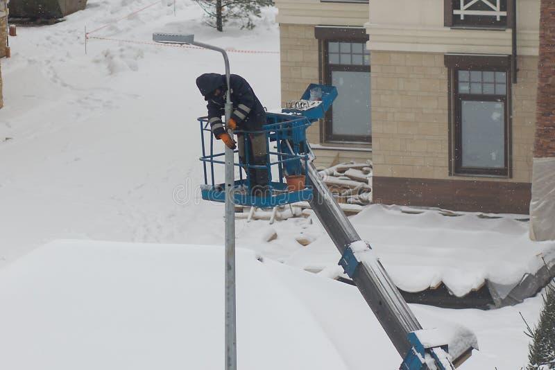 En arbetare installerar ett lyktaljus royaltyfri fotografi